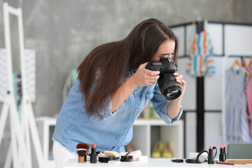 Young female blogger making photo of cosmetics at home