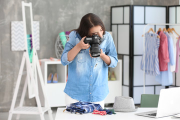 Young female blogger making photo of clothes at home