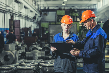 Two workers at an industrial plant with a tablet in hand, working together manufacturing activities