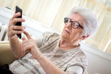 Confused old woman using smart phone at home.