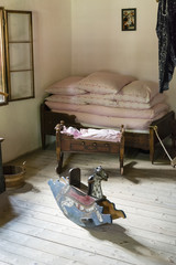 Interior of an old building with a rocking wooden horse, cradle and duvet.