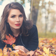 Autumn Woman Fashion Model with Fall Leaves Outdoors. Autumn Beauty