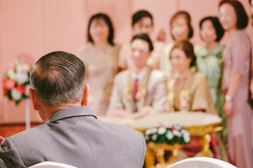 Bride's Father look at bride and groom in Thai traditional wedding. Family concept