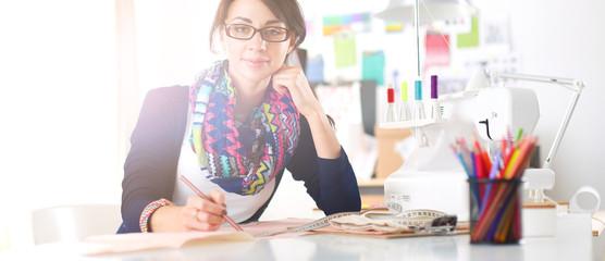 Beautiful fashion designer sitting at the desk in studio .