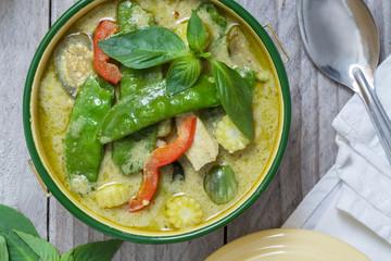 Grünes Thai-Curry in einer Schale auf Holztisch
