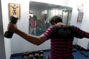 A picture of former California Governor Arnold Schwarzenegger decorates the wall as a man lifts weights at the Roopa sports club in Islamabad