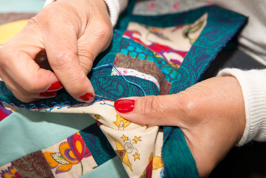 woman sewing for finish a quilt.