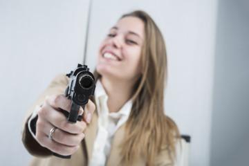 Bella impiegata seduta alla sua scrivania tutta in disordine ha una pistola davanti e guarda in macchina con aria di sfida