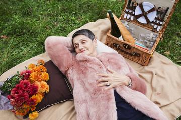 Portrait of a beautiful elderly woman lying on grass