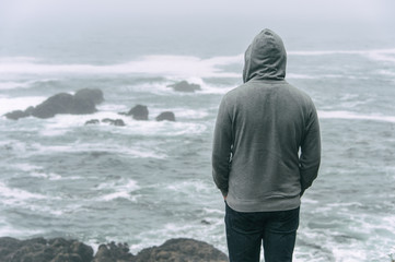 Man standing in front of the pacific ocean and looking at the stormy sea on Vancouver Island.