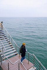 Girl in warm clothes standing on pier stairs.