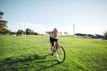 Vibrant mature woman enjoying herself on a bicycle