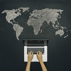 Internet search with notebook. World map on chalkboard.