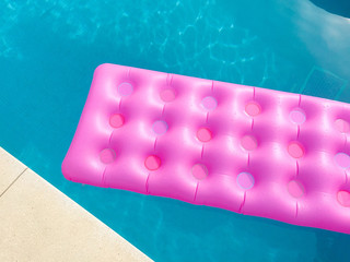 Bright pink lilo in swimming pool