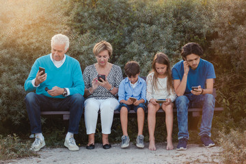Grandparents and their grand children all looking at their mobile phones