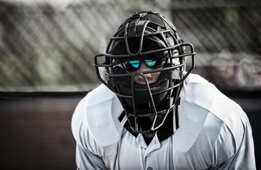 Umpire in face mask, behind home plate, looking at camera