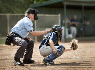 Umpire and catcher, just as ball hits catcher's mitt, dugout and players in background