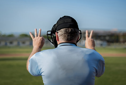 Back view of umpire making call at home plate