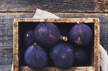 Purple figs in wooden crate with copy space on rustic wooden background