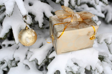 Gift box with golden bow and ball on snowy background
