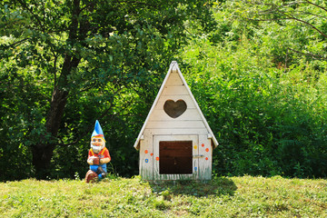 Small white dog house and a colorful dwarf