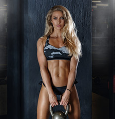 Beautiful fitness girl holding a dumbbell. Portrait.