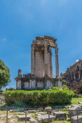 View of the various ruins of the Roman Forum with a very blue sky slightly cloudy without people in sight