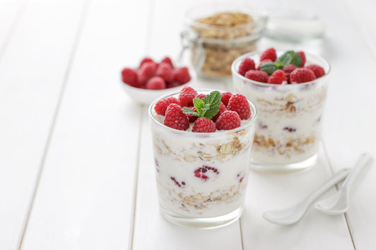 Healthy breakfast yogurt with granola and raspberries in glasses on white wooden table.