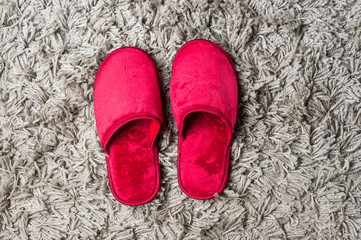 Red house slippers on gray carpet