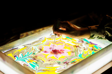 The master's hands perform the ebru technique. Drawing on the water.