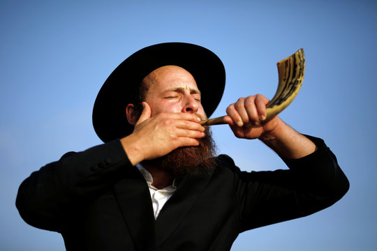 An ultra-Orthodox Jewish man blows a shofar, before he takes part in prayer a Tashlich prayer