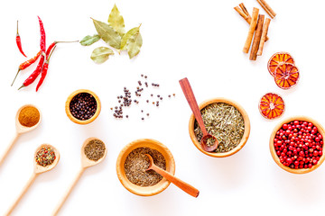 Kitchen table with spices and dry herbs on white kitchen background top view pattern