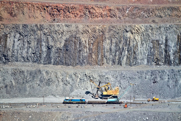 Excavator loading iron ore into goods wagon on the iron ore opencast mine. Krivoy Rog, Ukraine