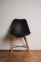 Black plastic chair against the white wall