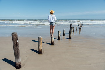 Young woman looking out at the waves of the ocean. Gulf coast.