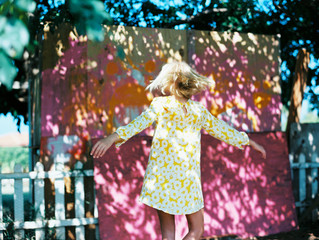 girl in yellow dress spinning on mixed shade and sun