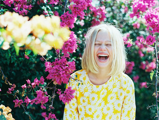 blonde girl laughing out loud in front of pink and yellow flowers