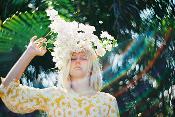 girl with white flowers over his head with rainbow flare