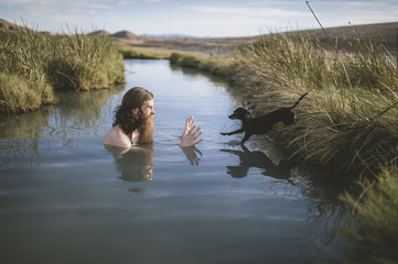 A handsome bearded man with his dogs in beautiful desert hot springs during the golden hour