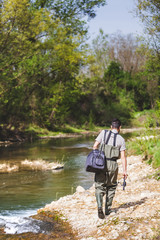 Fisherman with Equipment Bag Walking on a Bank of a Small River