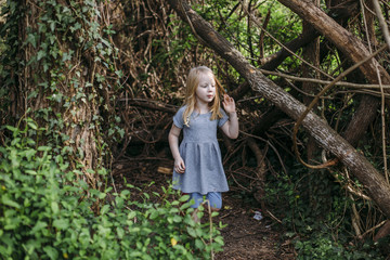 a young girl stands in the woods