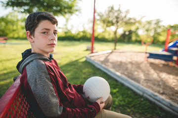 Teen boy holding a volleyball at park