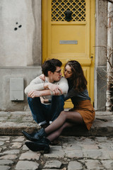 Young couple holding each other sitting on sidewalk in front of yellow door