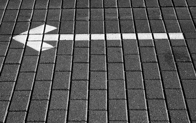 White arrow with left direction on cobble stone pavement.