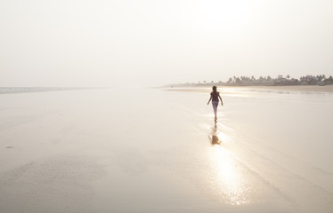 A lonely girl walking on a sea beach