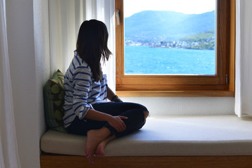 Young woman looking through the window to the Aegean sea