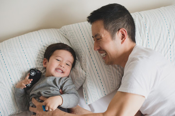 Dad tickling baby on bed
