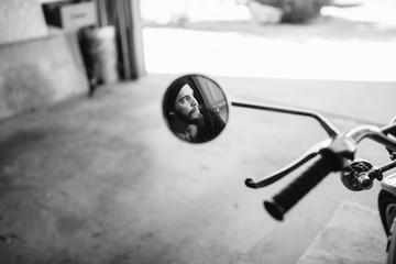 Young man's reflection in motorcycle mirror