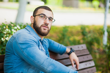 Handsome young man in glasses with beard relax outdoors
