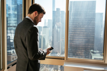 Young businessman checking his phone in an office with the view of the city in the background